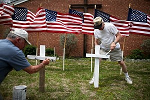Bob Gordon (L) and Bob Butler paint crosses they placed in front of 16 American flags as they build a memorial in front of Central Christian Disciples of Christ church for the victims of yesterdays shooting at Fort Hood