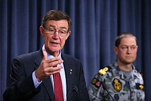 Chief Coordinator of the Joint Agency Coordination Centre, Air Chief Marshal Angus Houston (Ret'd) answers a question from a reporter as Commodore Peter Leavy of the Royal Australian Navy looks on during a press conference