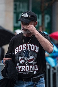 A man wipes his eyes while observing the site of the second explosion after the ceremony commemorating the one year anniversary of the 2013 Boston Marathon Bombing