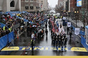 Boston area police and fire department flag bearers cross the finish line following the flag raising ceremony commemorating the one-year anniversary of the Boston Marathon bombings