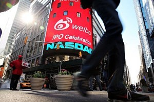 People walk by the Nasdaq exchange in Times Square
