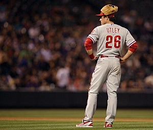Second baseman Chase Utley #26 of the Philadelphia Phillies wears his glove on his head as he awaits a pitching change in the seventh inning at Coors Field