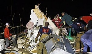 Emergency personnel search the remains of several mobile homes in Louisville, Miss., for survivors