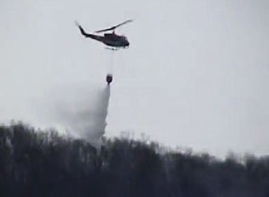 Helicopter drops water on a forest fire in Vernon