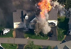A police SWAT team, left, is parked on the lawn of a home in Brentwood, N.H., as it explodes