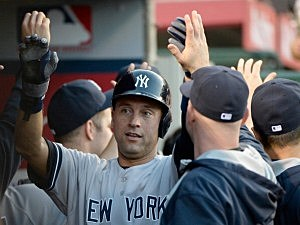 Derek Jeter #2 of the New York Yankees celebrates his homerun in the dugout
