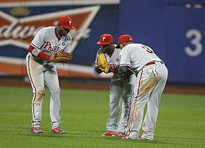 Domonic Brown #9, Jimmy Rollins #11, and Marlon Byrd #3 of the Philadelphia Phillies celebrate a 3-2 win against the New York Mets