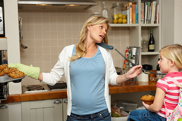 Pregnant Mother on Telephone Baking Muffins