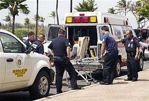 A 16-year-old boy, seen sitting on a stretcher center, who stowed away in the wheel well of a flight from San Jose, Calif., to Maui is loaded into an ambulance at Kahului Airport in Kahului, Maui, Hawaii