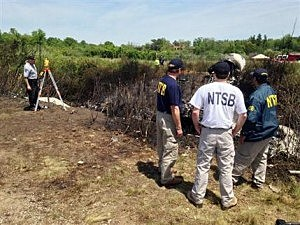 NTSB investigators at the scene of a plane that plunged down an embankment and erupted in flames during a takeoff attempt Saturday night at Hanscom Field in Bedford, Mass.
