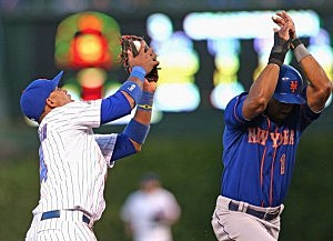 Luis Valbuena #24 of the Chicago Cubs makes a catch as Chris Young #1 of the New York Mets avoids a collision