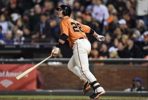 Buster Posey #28 of the San Francisco Giants watches the flight of his ball as he hits a two-run homer against the New York Mets