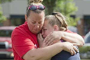 Parents of Reynolds High School students console one another in a nearby parking lot after word of a school shooting  in Troutdale, Oregon