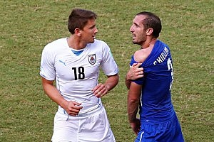 Giorgio Chiellini of Italy pulls down his shirt after a clash with Luis Suarez of Uruguay (not pictured) as Gaston Ramirez of Uruguay looks on