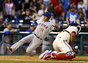 Ruben Tejada #11 of the New York Mets scores before the throw gets to catcher Carlos Ruiz #51 of the Philadelphia Phillie