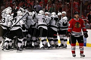 Ben Smith #28 of the Chicago Blackhawks skates away as the Los Angeles Kings celebrate after defeating the Blackhawks 5 to 4