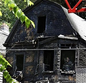Firefighters checked the remains of a burnt house for clues to determine the cause of a fire that authorities say killed six people in Newark