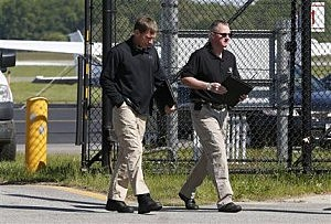 A federal investigator, left, and a state investigator leave the secure area at Hanscom Field in Bedford, Mass