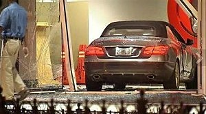 A man walks through the near a vehicle that crashed through the lobby entrance of CNN