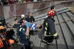 Paramedics, a police officer and a volunteer carry an injured man out from a subway station after a rush-hour subway train derailment in Moscow, Russia