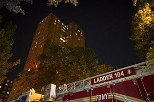 New York City firefighters work at the scene of a fire at public-housing high-rise in Brooklyn
