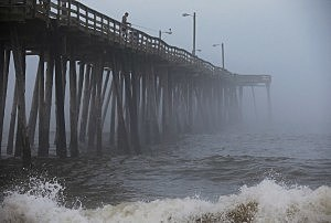 A man fishes from the Nags Head Pier as fog and heavy surf roll in, on July 3, 2014 in Nags Head, North Carolina.