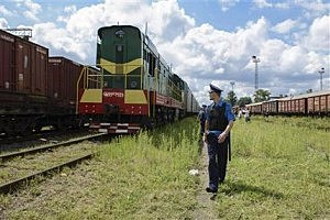 Police officers secure a refrigerated train loaded with bodies of the passengers of Malaysian Airlines flight MH17 as it arrives in a Kharkiv factory for a stop on Tuesday, July 22, 2014. The train carrying the remains of people killed in the Malaysia Airlines crash arrived in the eastern Ukrainian city of Kharkiv on Tuesday on their way to the Netherlands