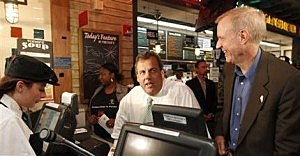 Gov. Chris Christie, middle, orders food at a  restaurant while Illinois Republican candidate for governor Bruce Rauner watches, during a campaign stop in Chicago