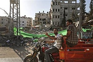 Palestinians drive past a building destroyed by an Israeli strike on Friday, in Gaza City
