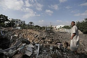 A Palestinian stands on the rubble of what used to be the house belonging to Muhammed Jmasy family, after it was destroyed by an overnight Israeli strike,  in Gaza City, northern Gaza Strip