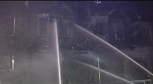 Firefighters pour water on a row home fire in southwest Philadelphia