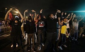 People defy a curfew before smoke and tear gas was fired to disperse a crowd protesting the shooting of teenager Michael Brown last Saturday in Ferguson, Mo