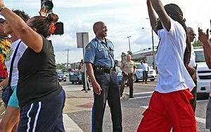 Capt. Ronald Johnson of the Missouri Highway Patrol smiles at demonstrators march along West Florissant Avenue in Ferguson, Mo