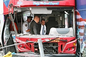 Officials inspect the driver's section of one of the two double-decker buses which collided together in Times Square