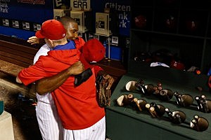 Ryan Howard #6 of the Philadelphia Phillies is met by A.J. Burnett #34 in the dugout after Howard hit a walk off home run in the bottom of the 15th inning