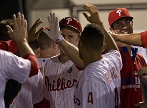 Second baseman Chase Utley #26 of the Philadelphia Phillies high fives his teammates after scoring a run in the bottom of the seventh inning