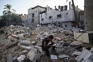 A Palestinian man reads items found in the rubble of a destroyed area of housing  in Gaza City, Gaza.