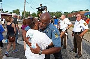 Capt. Ronald Johnson of the Missouri Highway Patrol hugs Angela Whitman in Ferguson, Missouri