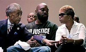 Rev. Al Sharpton, left, speaks with parents of Michael Brown, Michael Brown Sr. and Lesley McSpadden, right, during a rally at Greater Grace Church in Ferguson, Mo