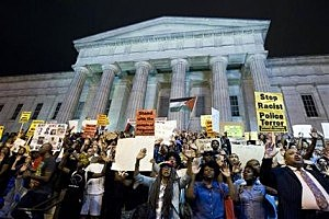 Demonstrators chant at the steps of the National Portrait Gallery in during a protest against the shooting of Michael Brown