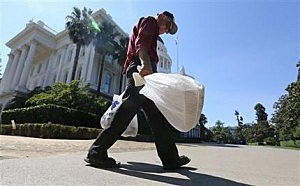Plastic single-use bags are carried past the State Capitol in Sacramento, Calif.