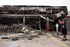 Passers-by and media take a closer look at the burned-out shell of the QuikTrip gas station torched during the violence that erupted in Ferguson, Mo.