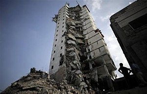 Palestinians inspect the damage to the Italian Complex following several late night Israeli airstrikes in Gaza City