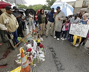 Rev. Jessie Jackson pauses at a makeshift memorial for Michael Brown  in Ferguson, Mo