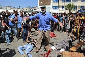 A man stands between dead and wounded Palestinians outside a UN run school in Rafah, in the southern Gaza Strip,
