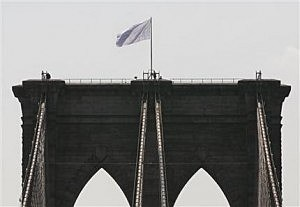 New York City police officers stand at the base of a white flag flying atop the west tower of the Brooklyn Bridge
