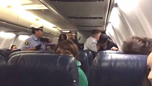 Police restrain a woman who began screaming onboard a USAirways plane at Philadelphia Int. Airport