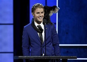 A monkey rests on Justin Bieber's shoulder as he speaks at the Comedy Central Roast of Justin Bieber