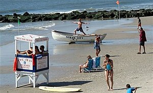 a lifeguard exercising atop a rowboat as people walk on the beach in Ocean City