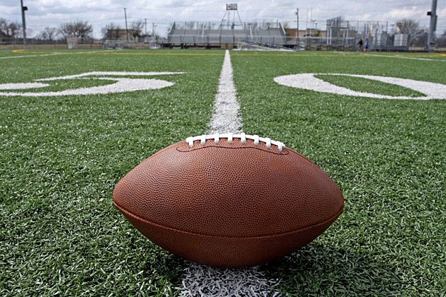 Football on Outdoor Field at the 50 Yard Line